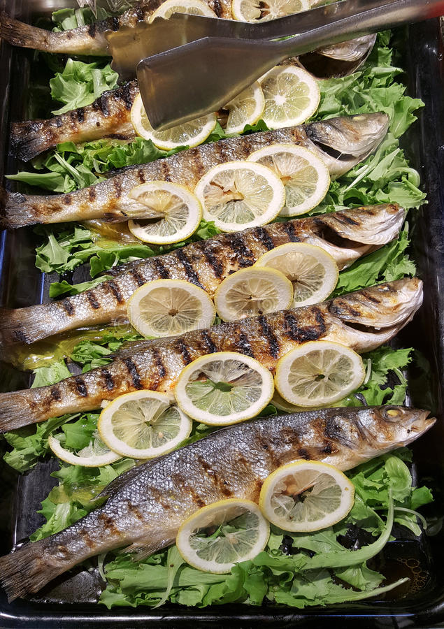 A Tray with grilled bass and lemon stock image