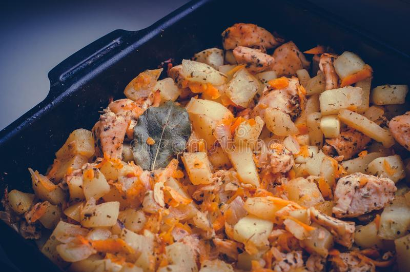 Tray of homemade meal with potatoes, meat, carrot, zucchini and bay leaf close up royalty free stock photos