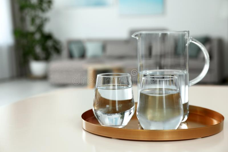 Tray with jug and glasses of water on white table in room. Refreshing drink. Tray with jug and glasses of water on white table in room, space for text royalty free stock photography