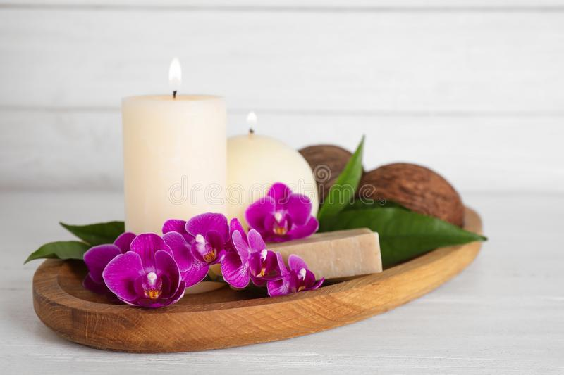 Tray with orchid flowers, candles and soap on wooden table stock photo