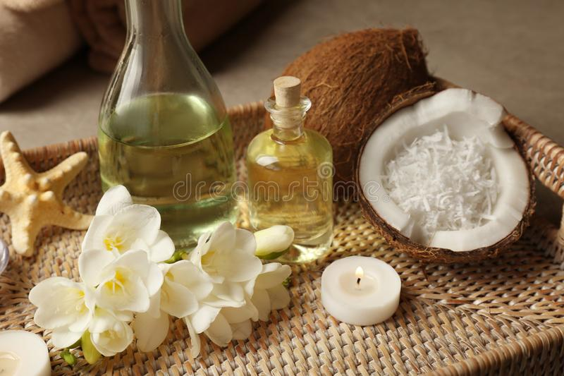 Tray with spa oil, coconuts, candle and flowers royalty free stock photography