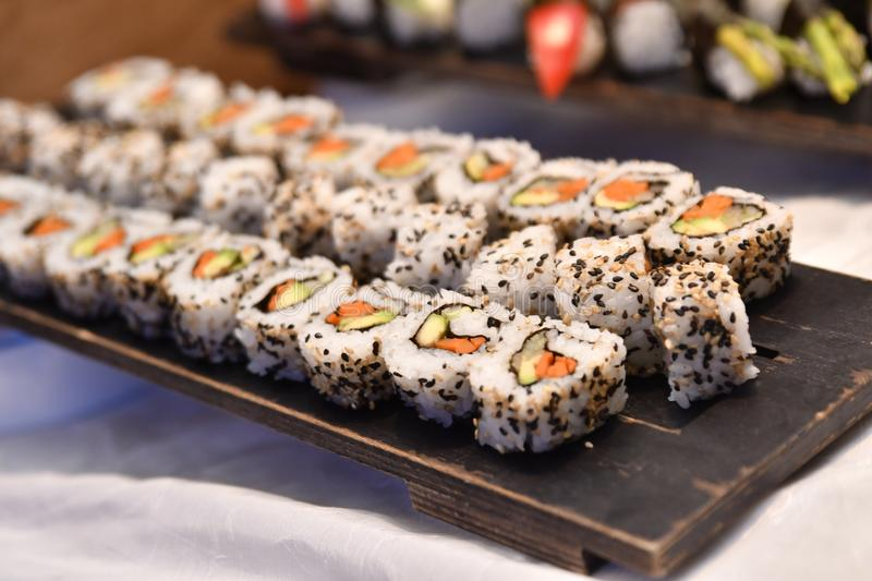 Tray of sushi. Close up of wooden tray with seed encrusted slices of fresh sushi roll royalty free stock images