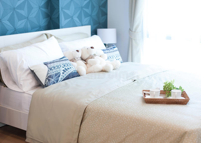 Tray with teddy bear, tea set and flower on the bed royalty free stock photo