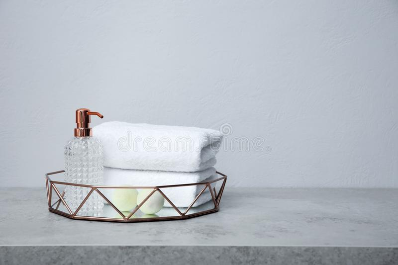 Tray with towels and toiletries on table. Against grey background stock photos