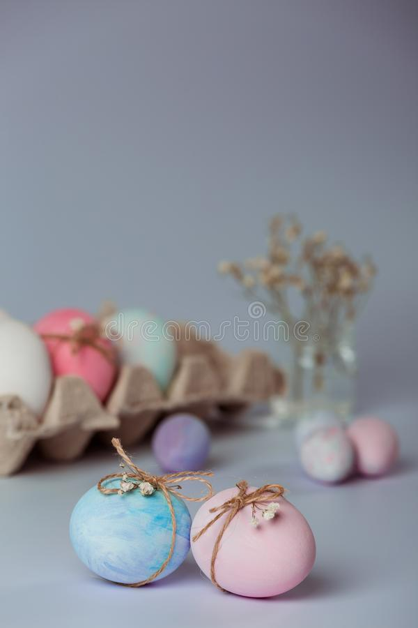 Two eggs. Decorating eggs. Easter is coming soon. Tray with white and pink eggs on a gray background. Blue and pink egg is decorated with a thread stock photos