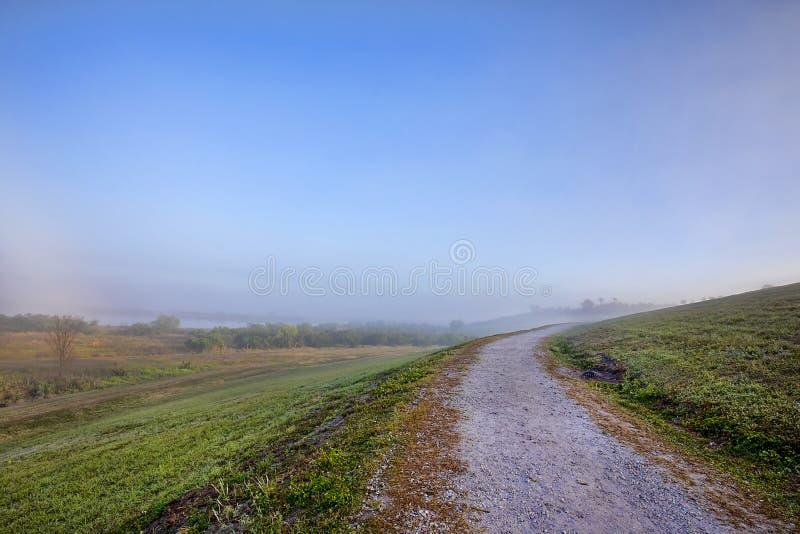 Trayectoria cuesta arriba que camina de la ladera en una mañana de niebla fotografía de archivo libre de regalías