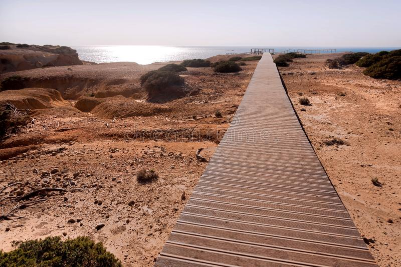 Trayectoria de madera a la playa soleada en la ciudad de Portugal Bahía brillante de Océano Atlántico en el área pacífica de Alga fotos de archivo
