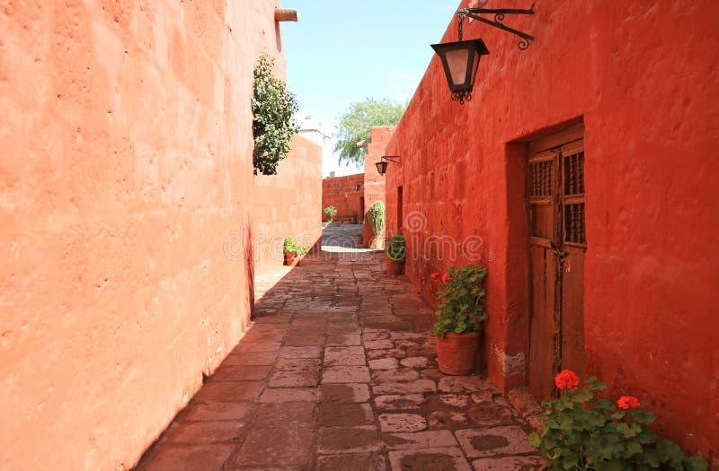 Trayectoria del guijarro entre edificios viejos del color rojo y anaranjado en el monasterio de Santa Catalina, Arequipa, Perú imagenes de archivo