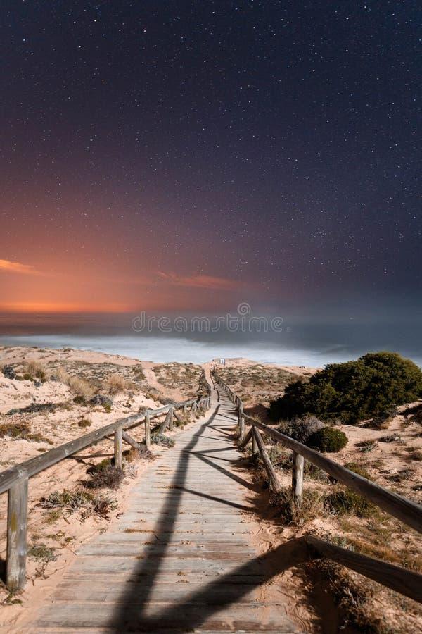 Trayectoria a la playa con el cielo estrellado foto de archivo