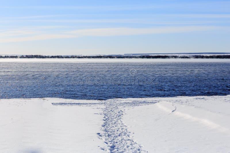 Trayectoria pisada en la nieve al agua Lago no congelado en el invierno foto de archivo libre de regalías