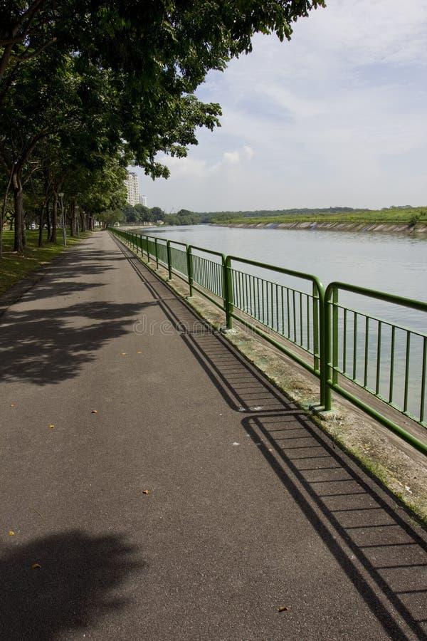 Trayectoria que camina y de ciclo por el río imagen de archivo