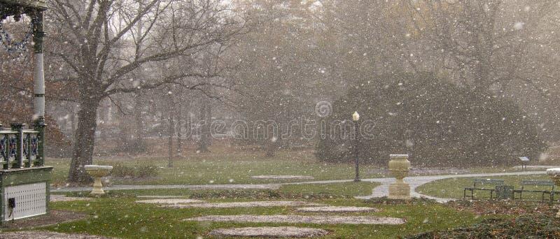 Trayectoria y bancos vacíos en jardines públicos durante ráfaga de nieve con la charca en fondo imagen de archivo