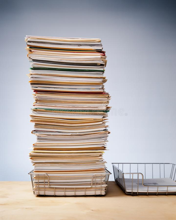 Trays auf dem Schreibtisch mit einem ehrgeizigen Stapel nie endender Papierarbeit stockbild