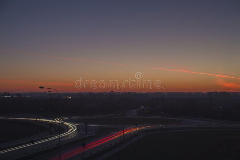 Trazalíneas de la calle de la opinión de la noche con puesta del sol mágica en la ciudad de Letonia Daugavpils fotografía de archivo libre de regalías