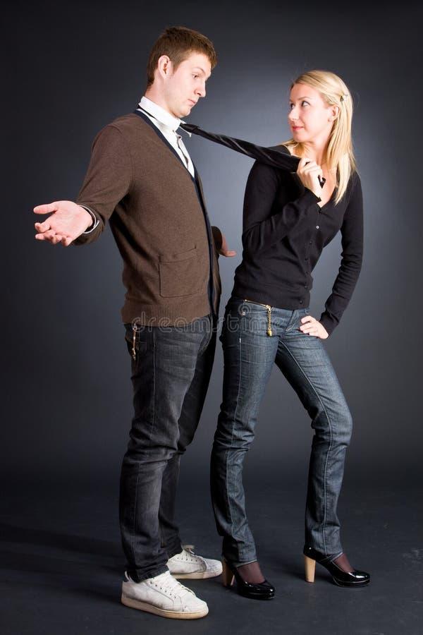 Trazione delle donne uomini da una cravatta immagini stock libere da diritti
