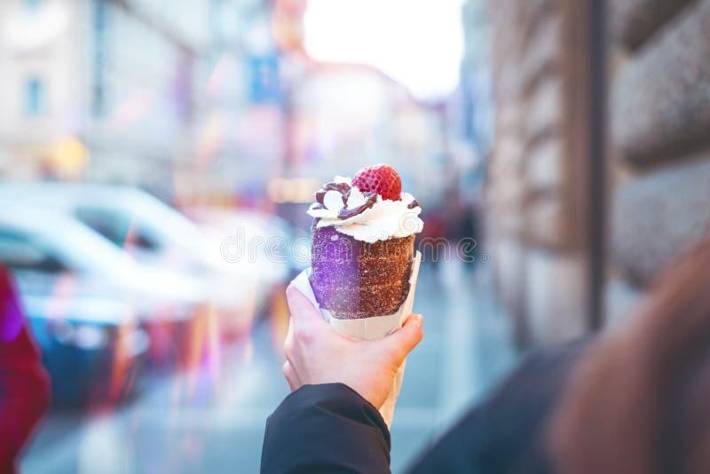 Trdelnik eller trdloen är den traditionella tjeckiska sötsaken Trdlo för kvinnahanduppehälle i den Prague gatan Gatamat arkivbilder