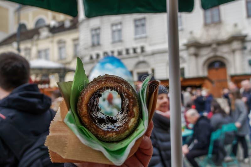Trdelnik o postre dulce de la torta del escupitajo según lo servido en un mercado de la comida del aire abierto en Viena, Austria imagenes de archivo