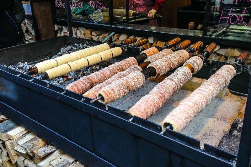 Trdelnik, traditioneel die dessert in een open brand houten staak wordt gebakken in Kerstmismarkt van Praag royalty-vrije stock afbeeldingen