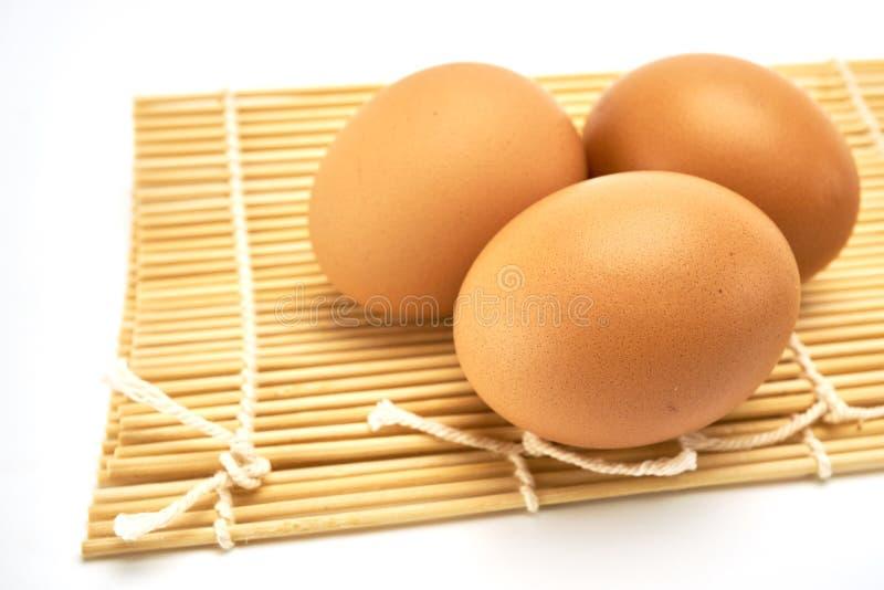 Tre ägg på matt bambu royaltyfri foto