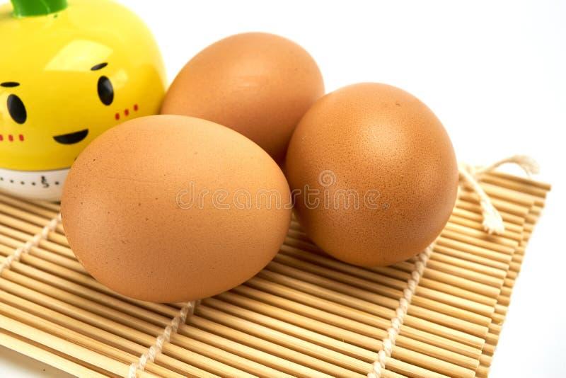 Tre ägg på matt bambu arkivbild
