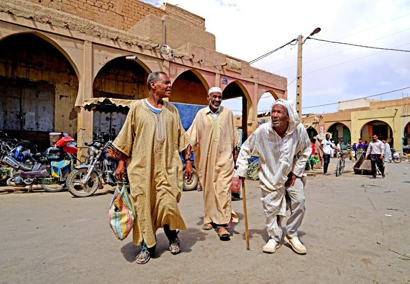 Tre äldre Berbermän går till souk av staden av Rissani i Marocko arkivfoton