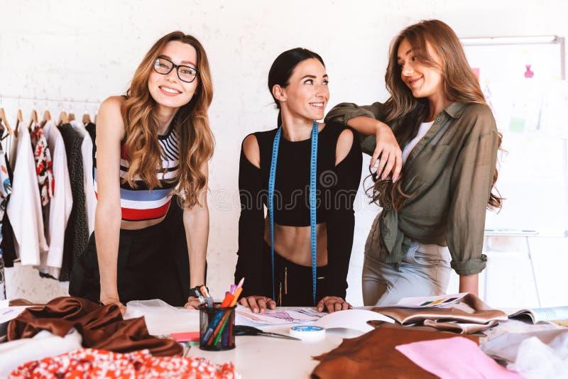 Tre älskvärda kläderformgivare för unga kvinnor fotografering för bildbyråer