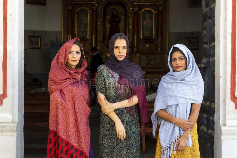 Tre älskvärda latinamerikanska brunettmodeller poserar i en katolsk kyrka fotografering för bildbyråer