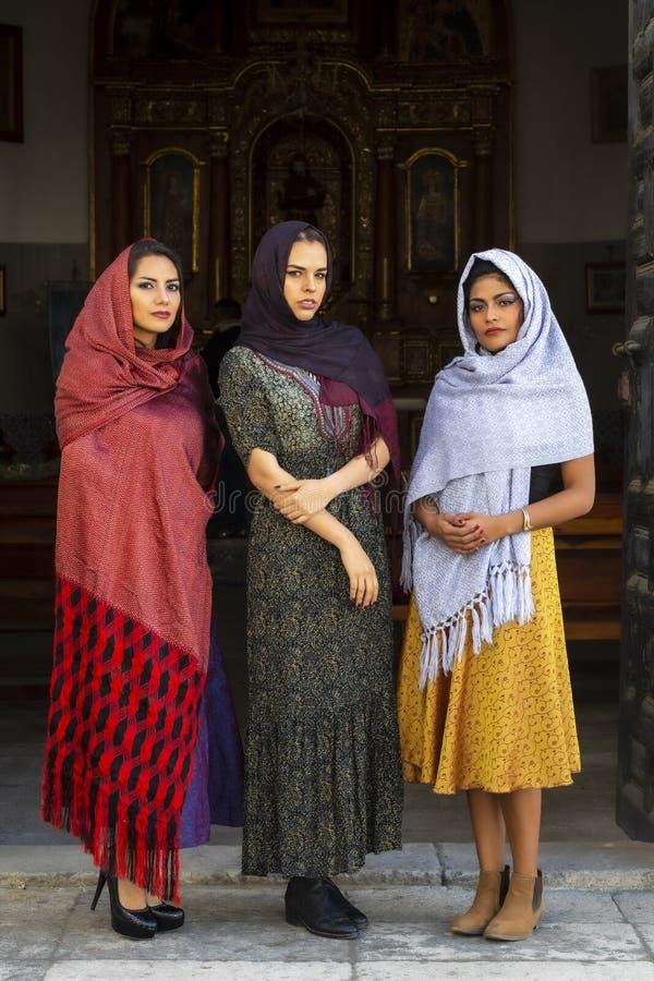 Tre älskvärda latinamerikanska brunettmodeller poserar i en katolsk kyrka royaltyfri fotografi