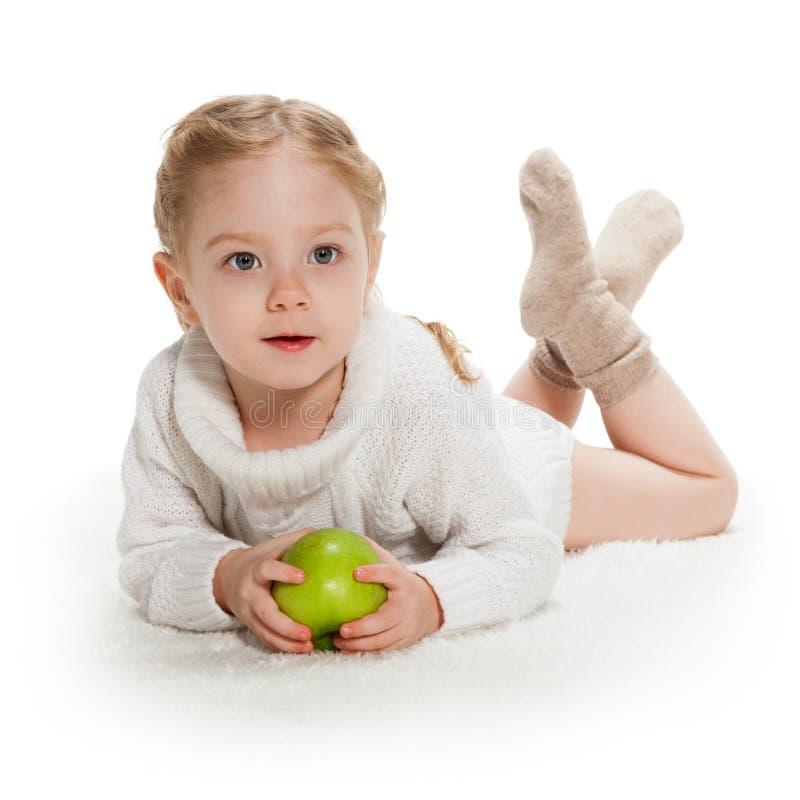 Tre-år gammal flicka med det gröna äpplet royaltyfria foton