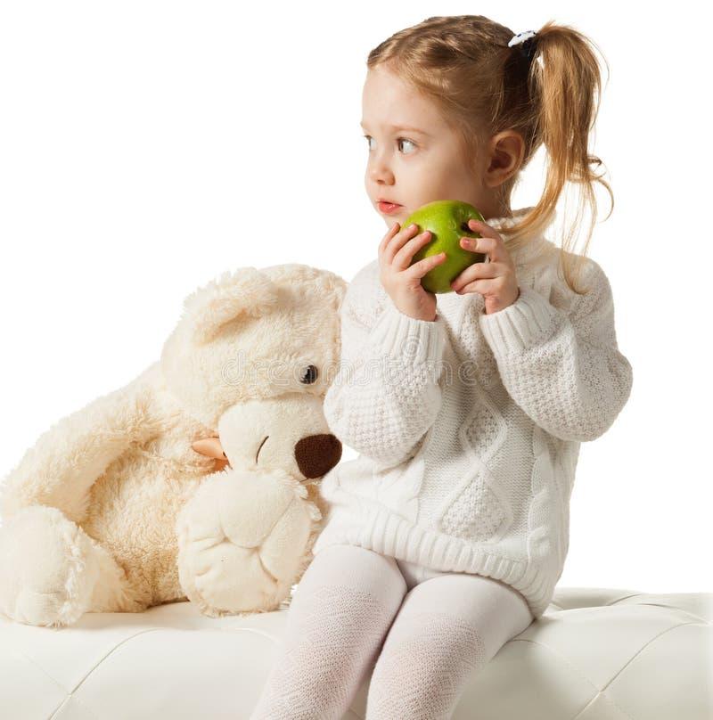 Tre-år gammal flicka med det gröna äpplet royaltyfri bild