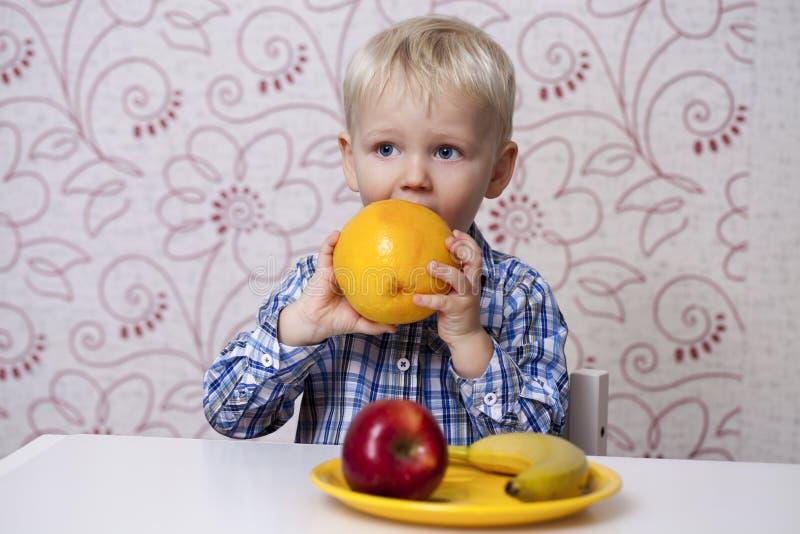 Tre-året pojken äter en gul grapefrukt royaltyfri foto