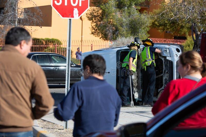 Tre åskådare bevakar räddningstjänsten och rensar en kraschad minister royaltyfri bild