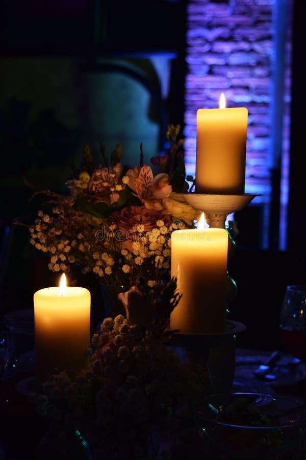 Tre Ñ-andles i mörkret, bukett av blommor som gifta sig dekoren royaltyfri foto