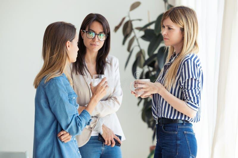 Tre abbastanza giovani donne di affari che bevono caffè mentre prendere per irrompere l'ufficio immagine stock