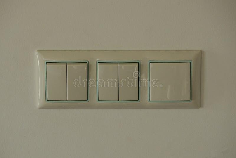 Tre accendere di plastica grigi la parete bianca nella stanza fotografie stock