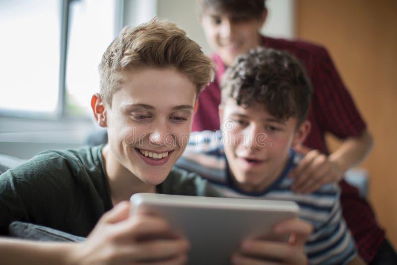 Tre adolescenti che giocano gioco sulla compressa di Digital a casa immagini stock libere da diritti