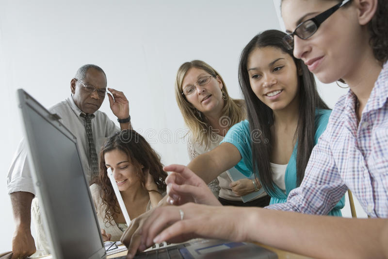Tre adolescenti che per mezzo del computer portatile. fotografia stock