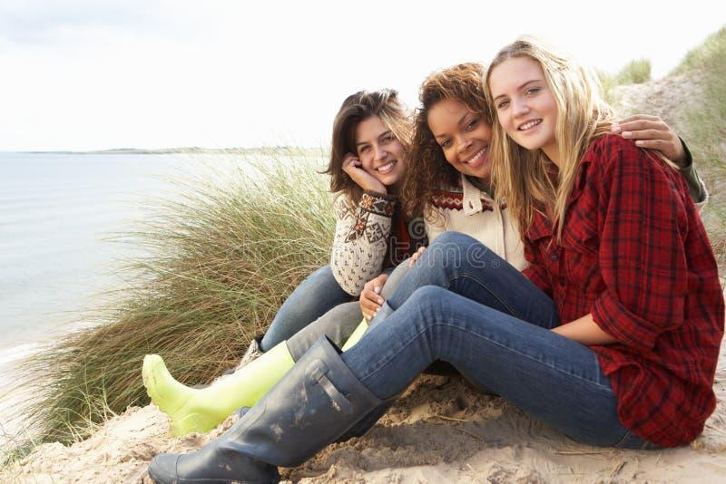 Tre adolescenti che si siedono in dune di sabbia immagine stock libera da diritti