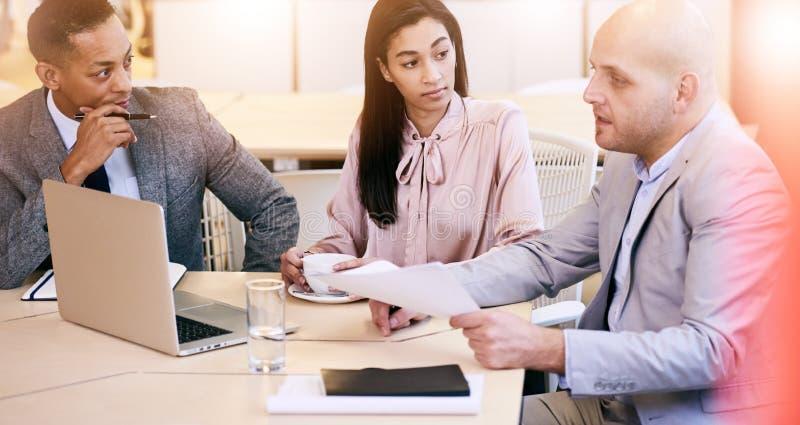 Tre affärsledare som meddelar under möte i konferensrum arkivfoton