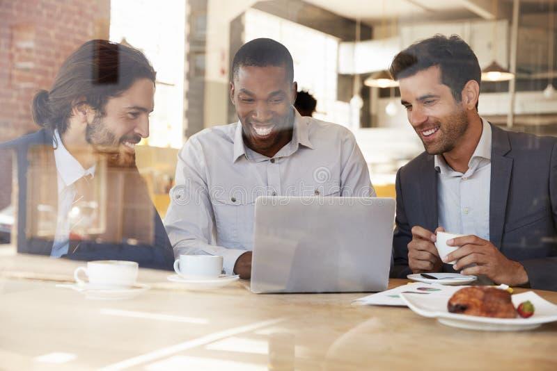 Tre affärsmän som möter i coffee shop som skjutas till och med fönster royaltyfri bild