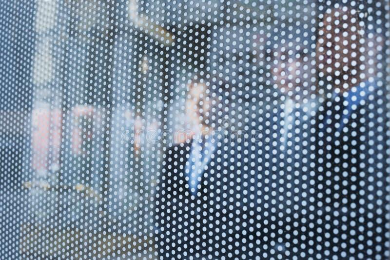 Tre affärspersoner bak en glasvägg som ut ser, oigenkännliga framsidor fotografering för bildbyråer