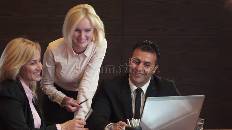 Tre affärspersoner diskuterar aktivt vad de ser i deras bärbar dator royaltyfri bild