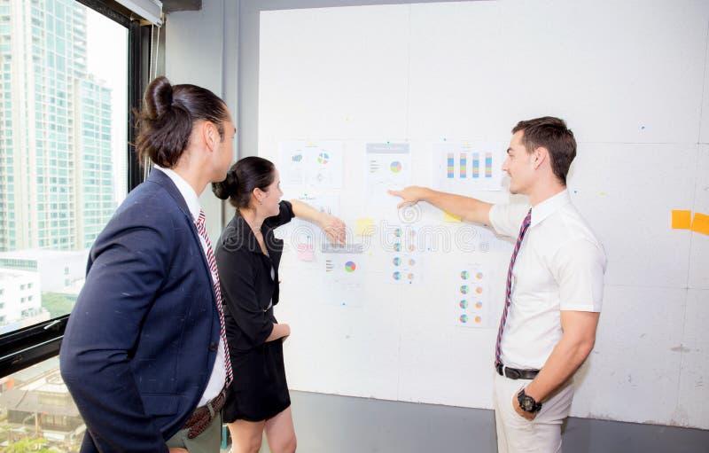 Tre affärspersoner i det moderna kontoret som ser rapporten och analyserar med samtal i mötesrum royaltyfria foton