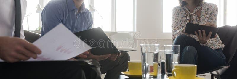 Tre affärspersoner i ett kontorsmöte arkivbild