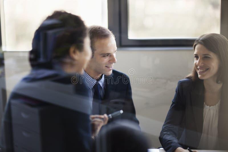 Tre affärspersoner som sitter och diskuterar på ett affärsmöte arkivbild