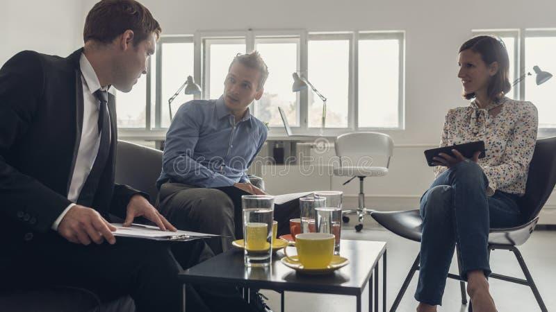 Tre affärspersoner som sitter runt om en kaffetabell arkivfoto