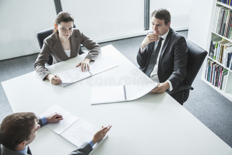 Tre affärspersoner som sitter runt om en tabell och har ett affärsmöte, sikt för hög vinkel royaltyfri fotografi