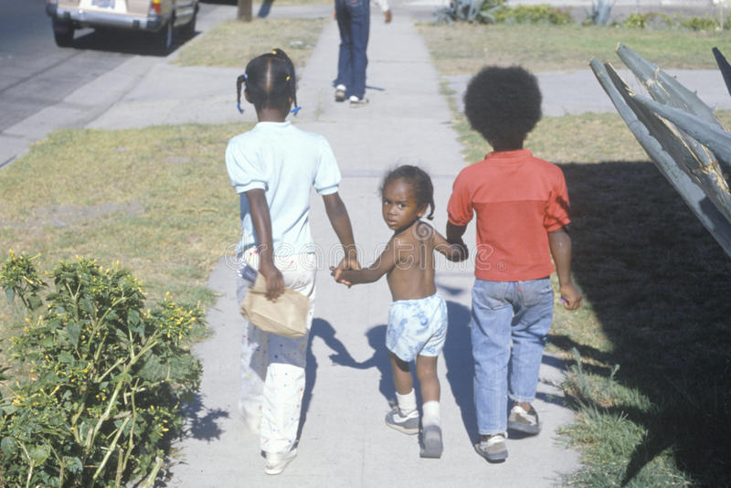 Tre afrikansk amerikanbarn som hem går, södra central, Los Angeles, CA royaltyfri bild