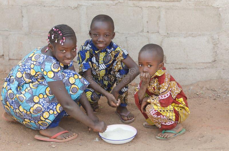 Tre afrikanska barn som sitter äta utomhus ris i Afrika royaltyfri fotografi