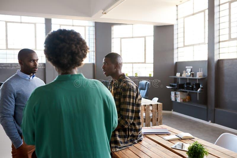 Tre afrikanska coworkers som tillsammans talar i ett modernt kontor fotografering för bildbyråer